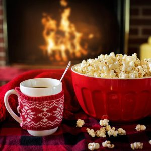 warm and cozy mug and popcorn in front of a fire